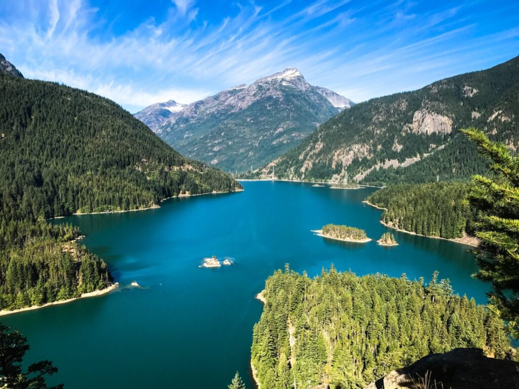 A bright blue lake sits between steep mountains covered with evergreen trees and rocky ridges.