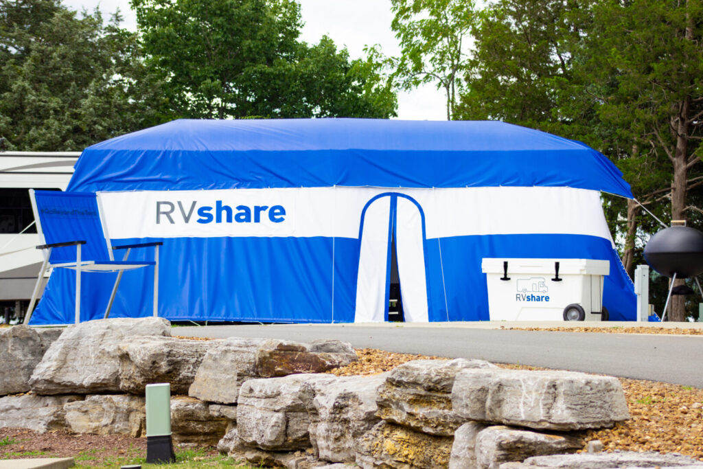 RV with large tent draped over it alongside an oversized camping chair and cooler