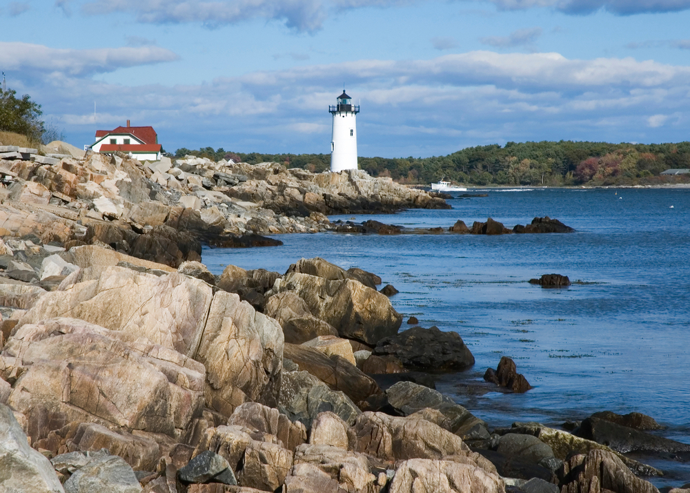 A white lighthouse stands on the rocky shore next to deep blue water, a tug boat sailing in the distance. The shore is surrounded with densely forested banks under a blue sky with white clouds.
