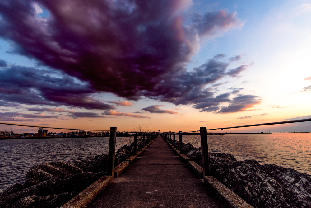 A dramatic sunset turns the sky purple and orange over a harbor, a long paved pier with rocky edges leading out into the water.