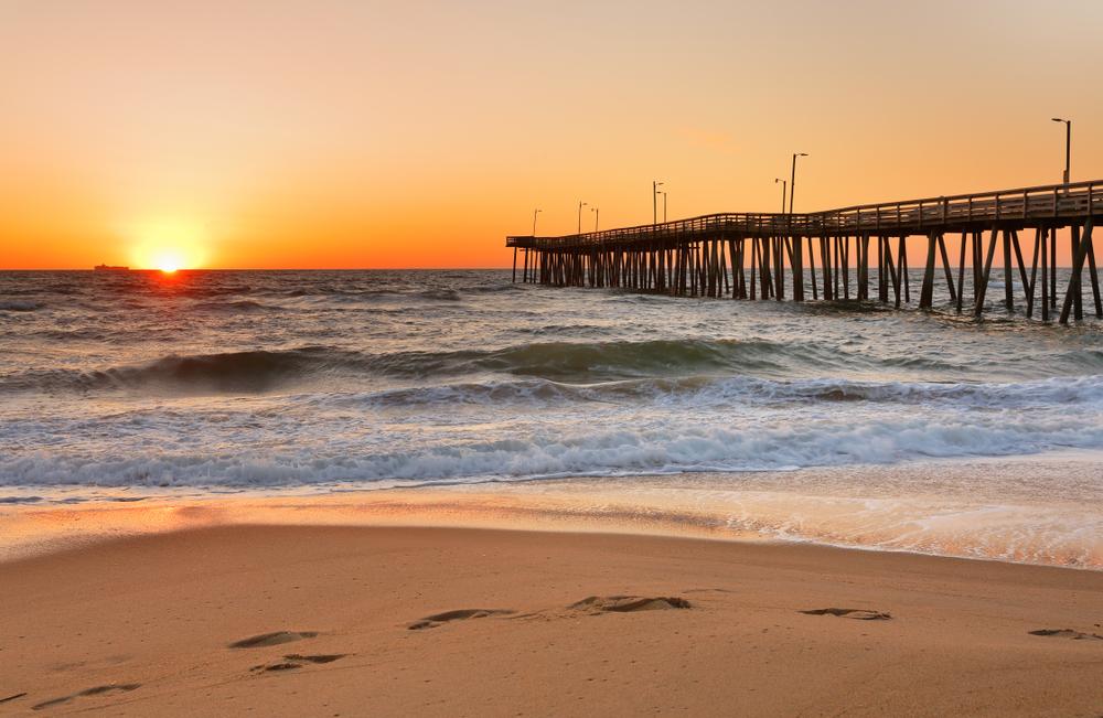 A long wooden pier stands above a ocean, waves crashing toward the shore as the sun sets over the horizon.