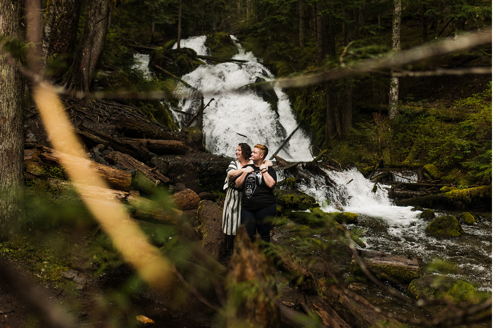 couple embraces at zigzag falls in oregon