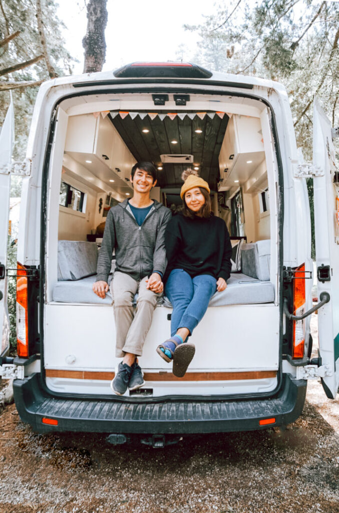 Young couple sits in the back of their campervan