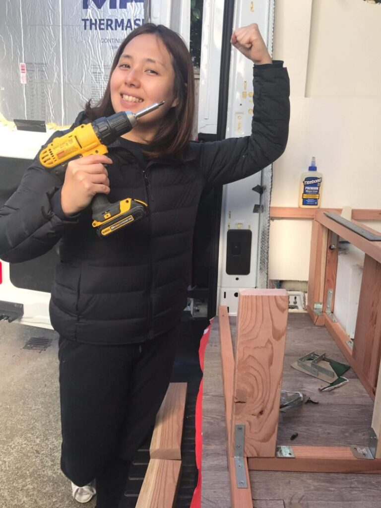 Woman holds drill while working on her campervan
