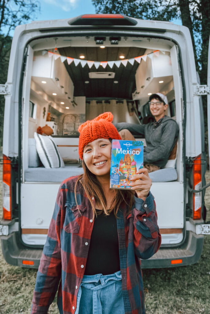 Woman holds a travel guide to Mexico with her campervan and boyfriend in the background