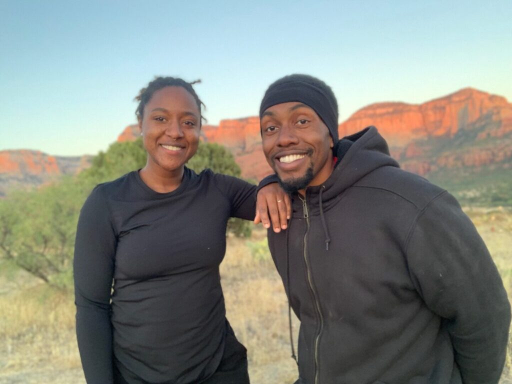 Couple smiles and poses together in a desert