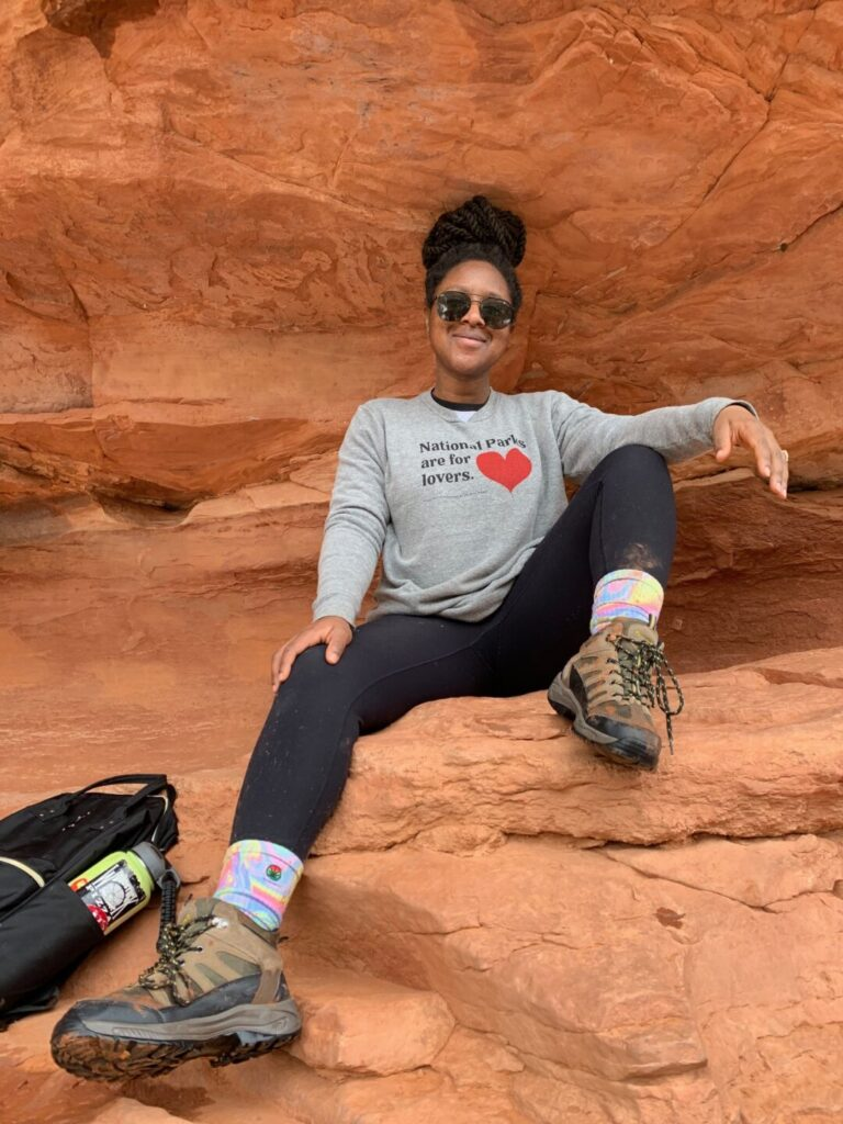 Woman poses on red rocks while hiking