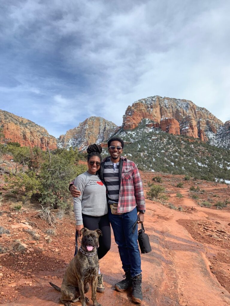 Couple and their dog poses in a desert