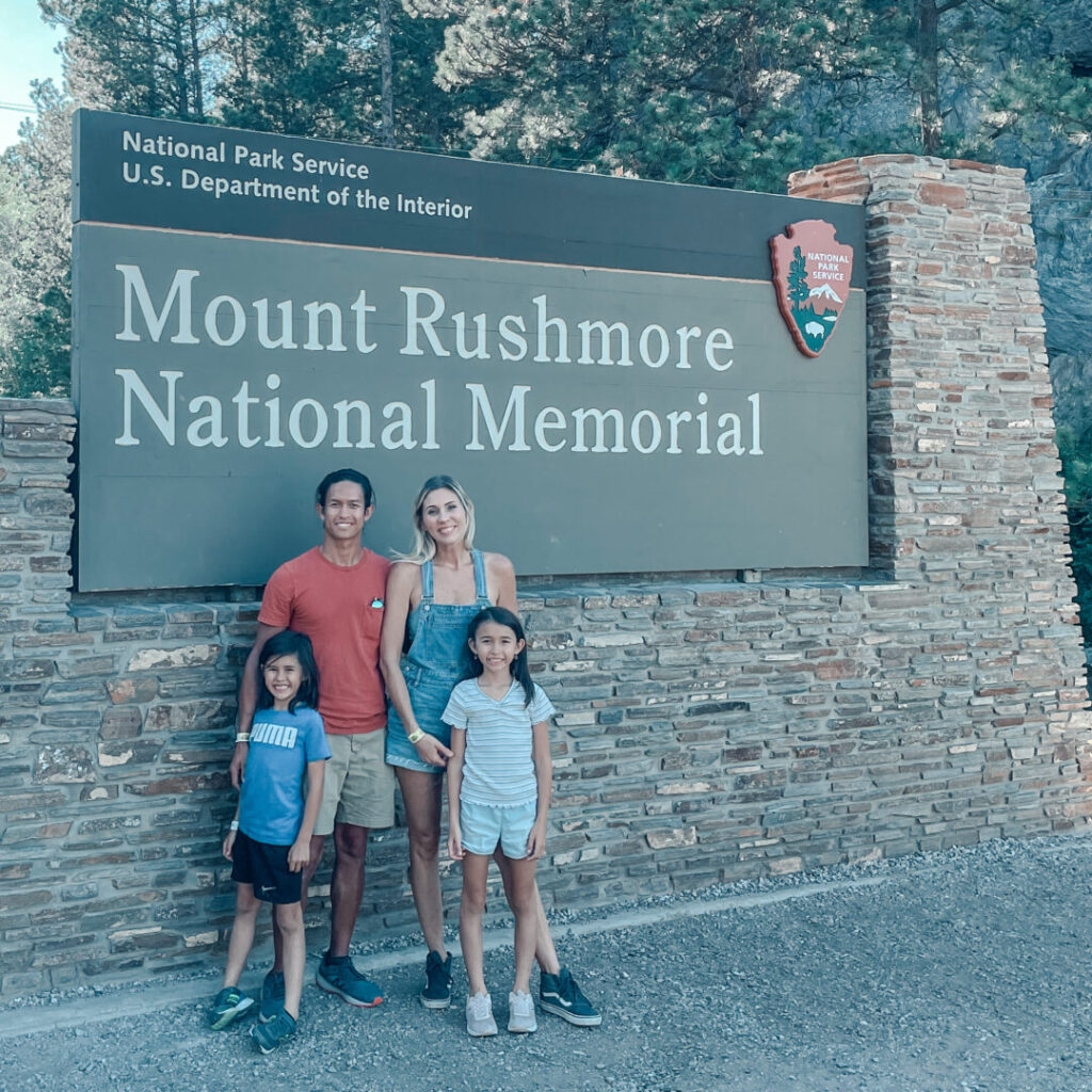 Family poses in front of Mount Rushmore National Memorial sign