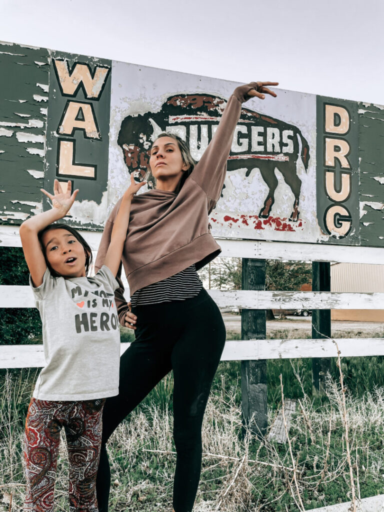 Mom and child pose in front of sign for Wall Drug