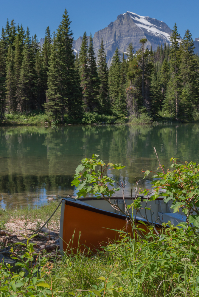 Orange canoe hidden in the brush along a mirror-still forested lake with a mountain rising in the background along the Swiftcurrent trail in Glacier National Park in the American state of Montana.