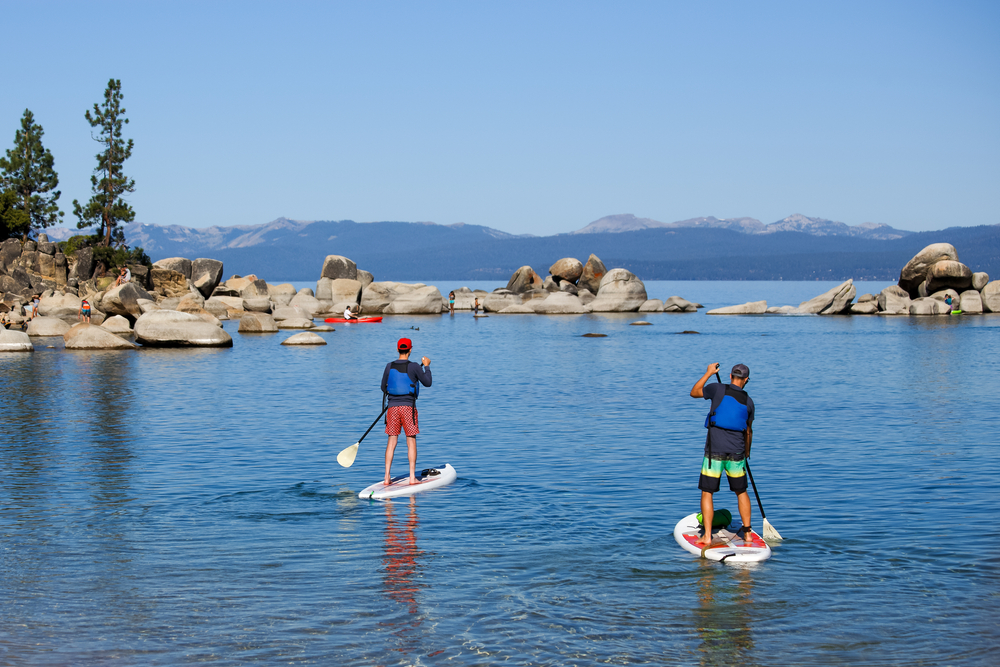 Two young men wearing life jackets paddle boarding on a lake with a mountain and boulder backdrop.