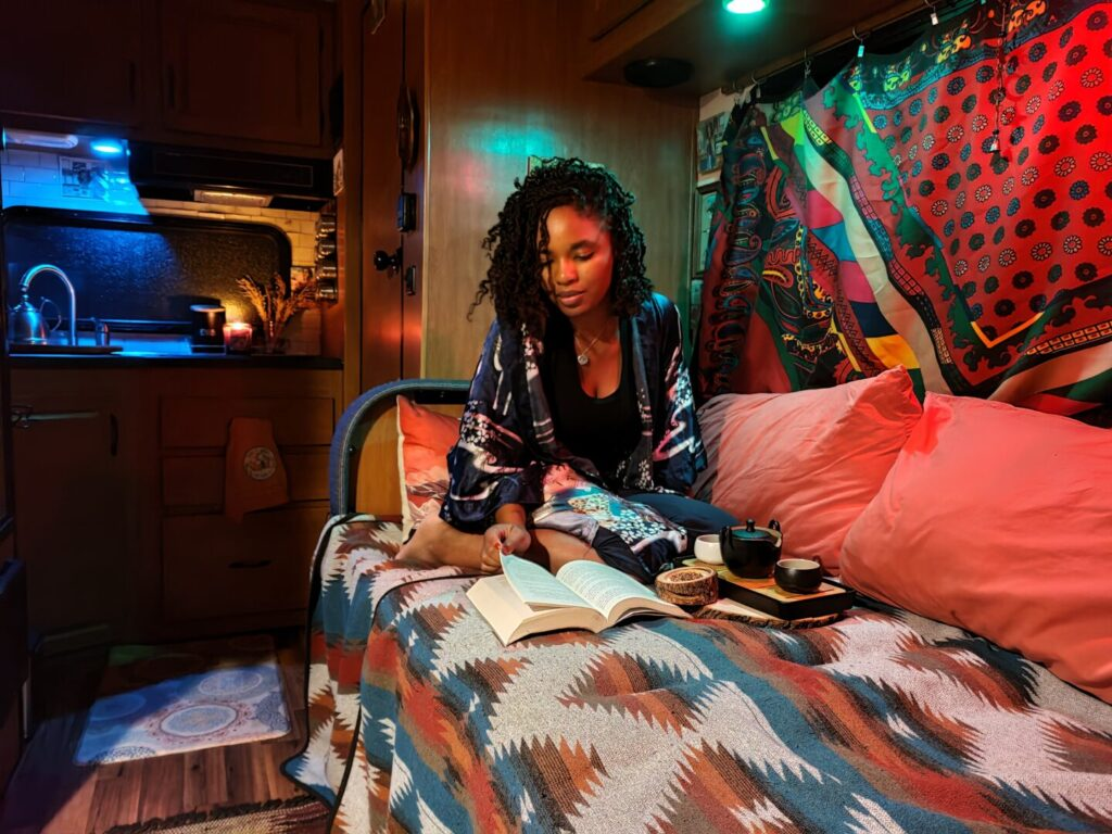 Bedroom of Class C RV lit with colored lights