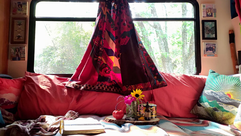 Interior couch of an RV with decorated elements such as fresh flowers and pillows
