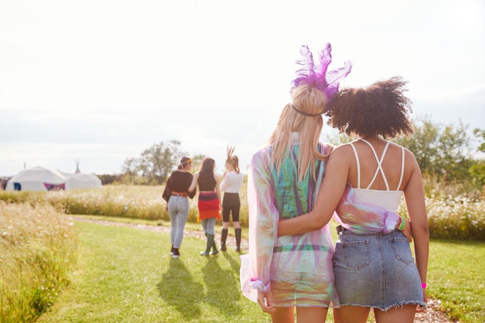 Two women walking towards their campsite