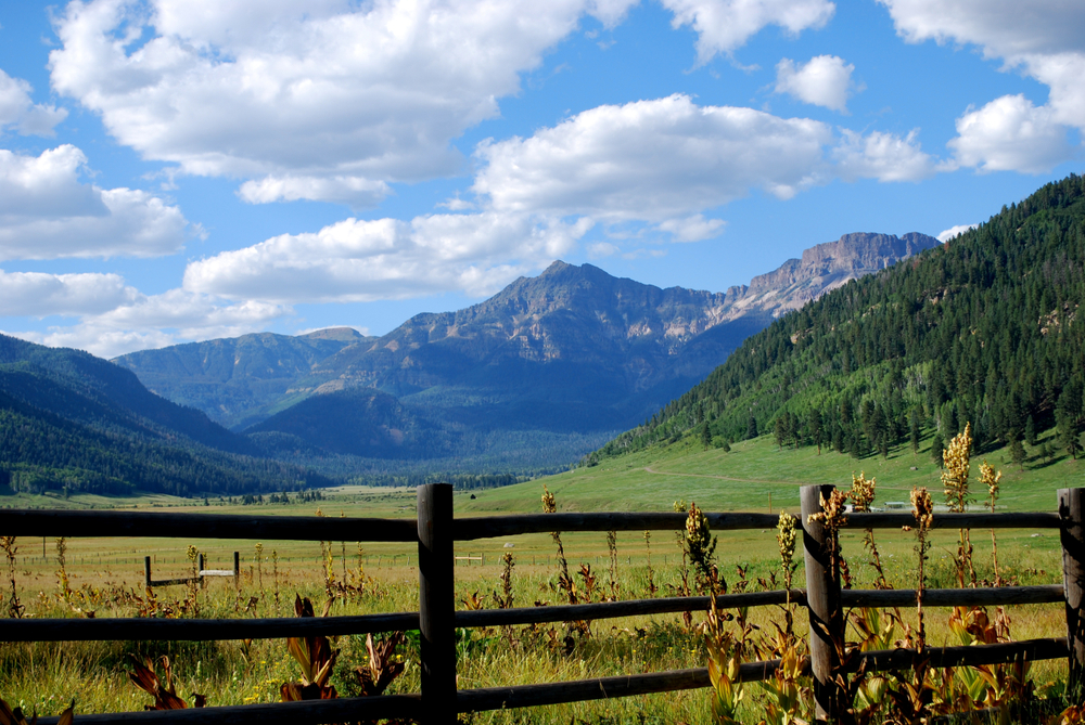A wooden fence in a grassy field. Tall mountains stand in the background under puffy white clouds in a blue sky