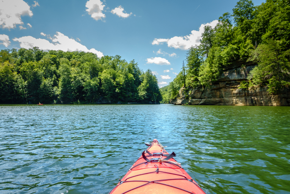 The front of a red kayak floating in a lake surrounded by tall green trees