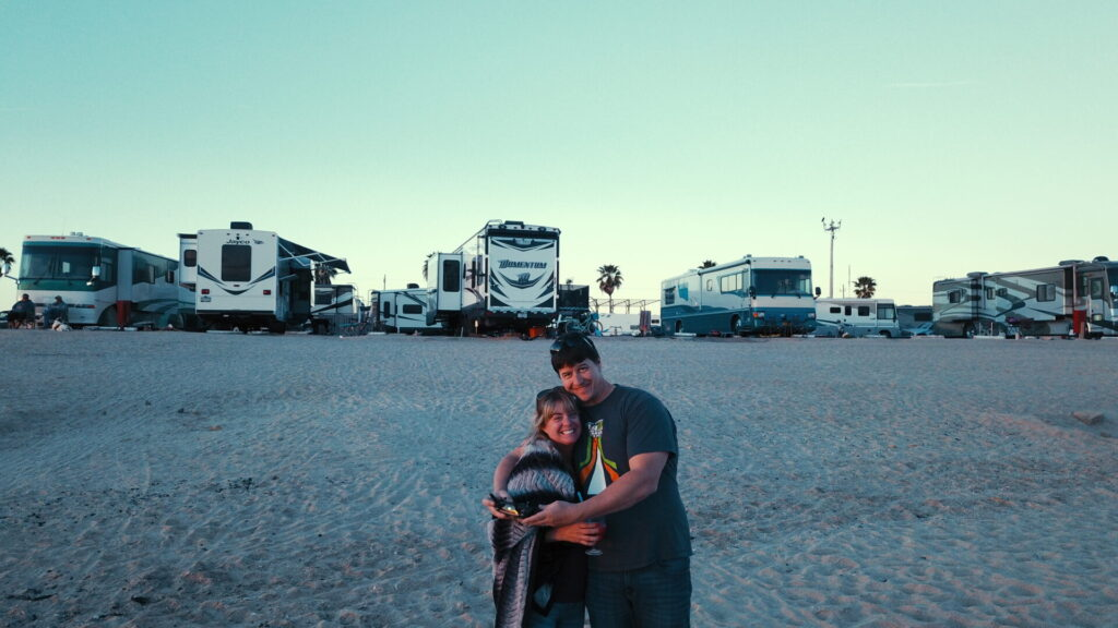 Couple on the beach standing in front of RVs