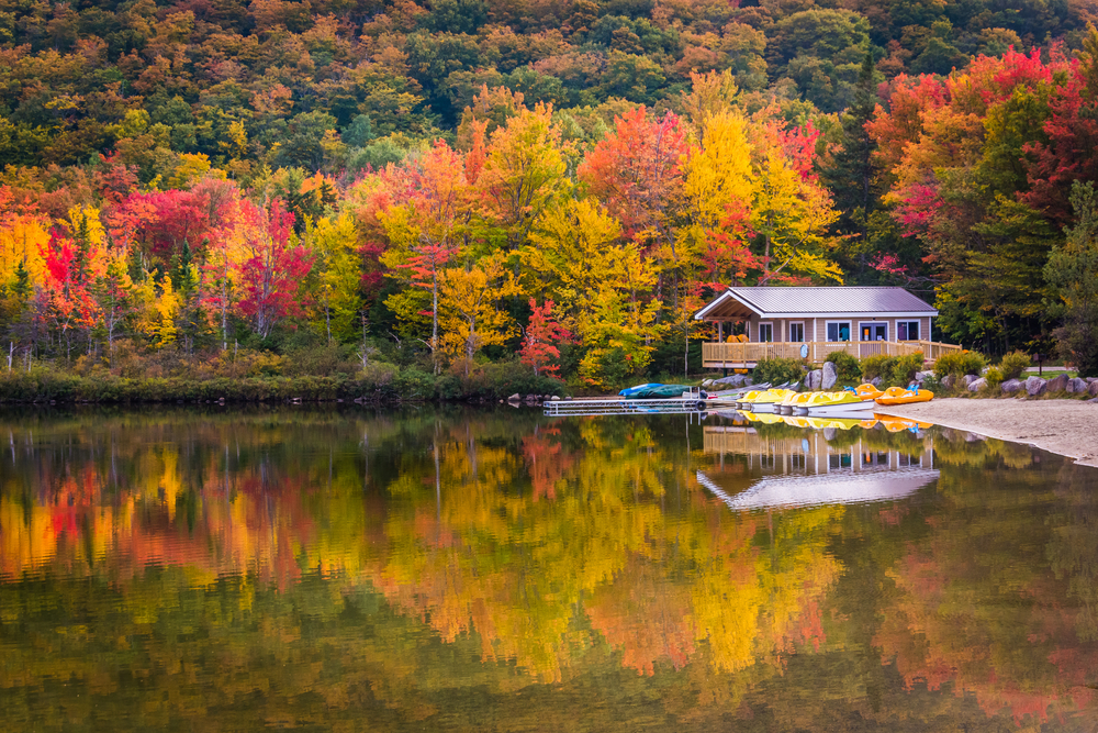 A boathouse on the edge of a lake that reflects the surrounding red, orange, and yellow colors of the trees