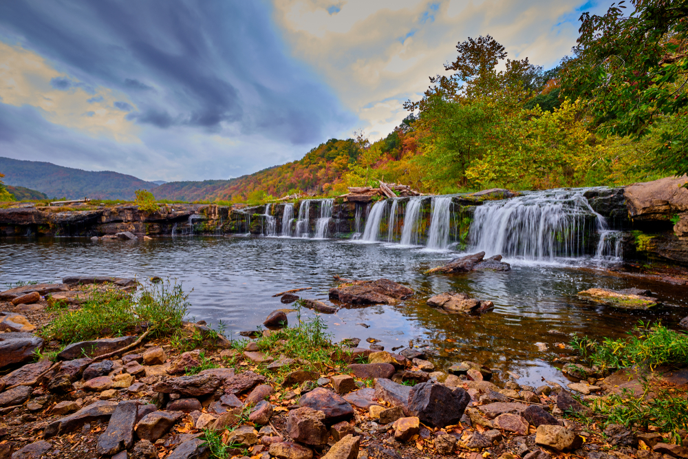 Water falls over a short rocky cliff. Boulders and rocks sit in the water below. Tall green and autumn colored trees stand on top of the cliff. Mountains can be seen in the distance.
