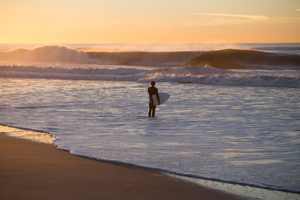 Surfer about to paddle out in high surf. Photographed in Rockaway Beach, Queens, New York, in October 2015.