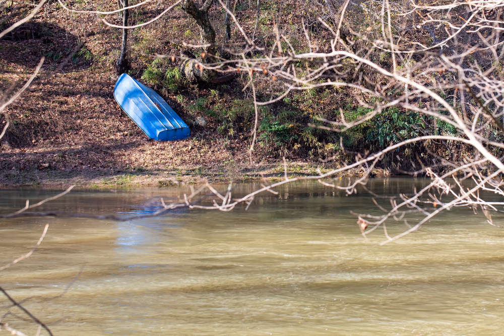 Small blue metal boat rests upside down on the western bank of the Yadkin River in Wilkes Couny, North Carolina.