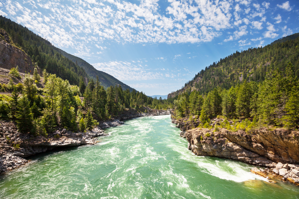 A blue-green river rushes through a valley of rocky mountains covered in tall green trees.