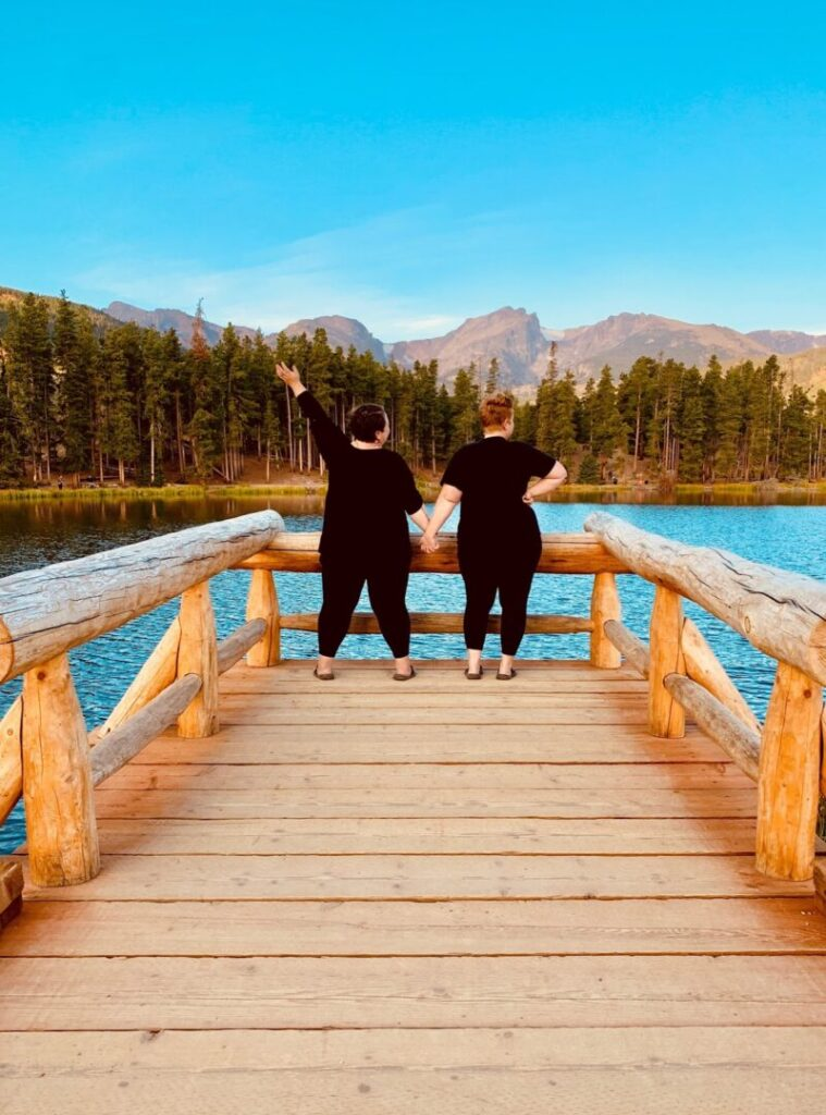 Women stand at the end of a pier holding hands looking over a lake