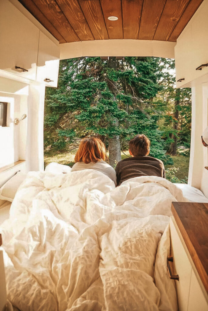 Couple lays in bed looking out the back of their open campervan doors
