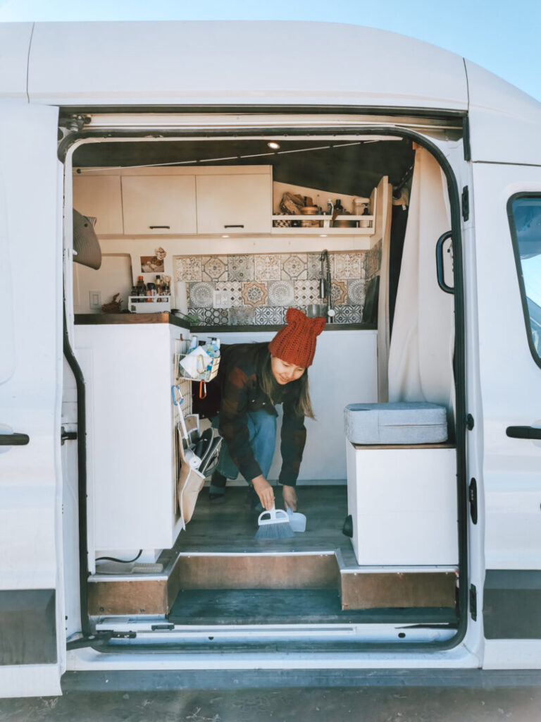 Woman cleans the inside of her campervan