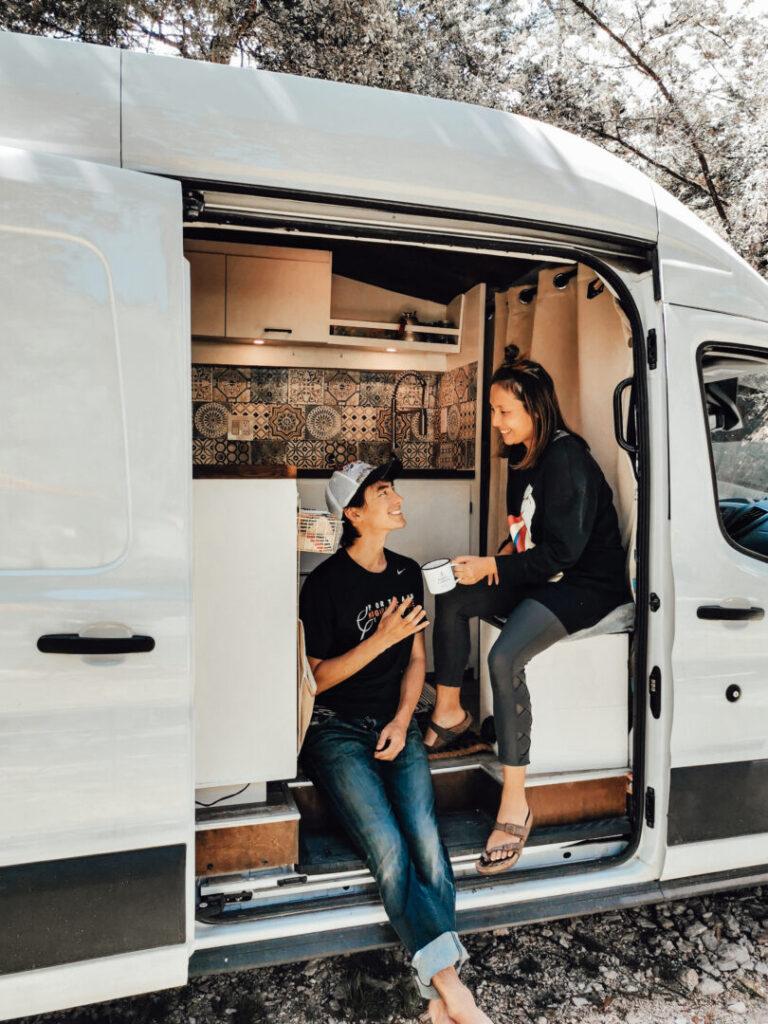 Couple drinks coffee inside the open door of their campervan
