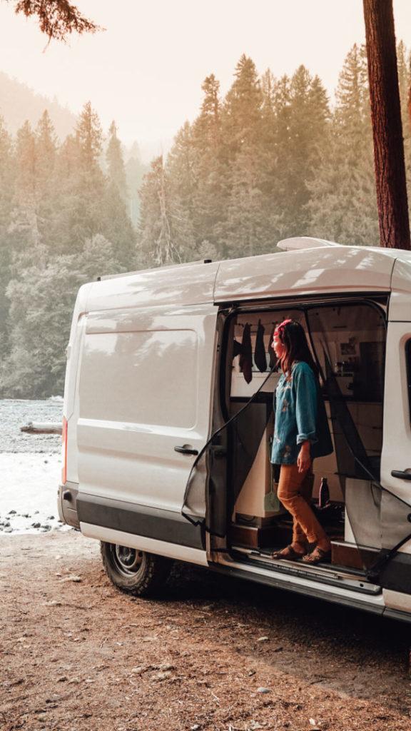 Woman stands in the open door of her campervan