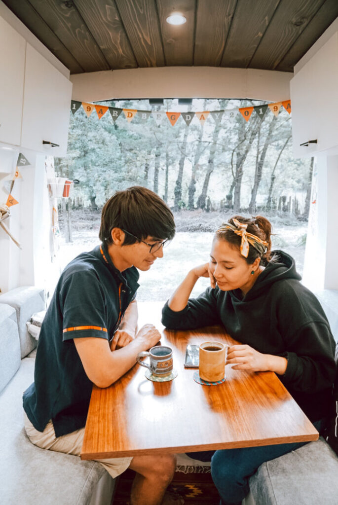 Couple at a table in their campervan