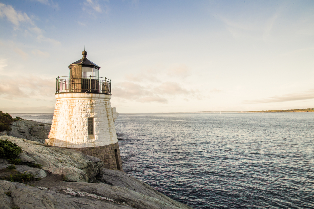 A white painted brick lighthouse on the edge of a gray rocky cliff overlooking the sea.