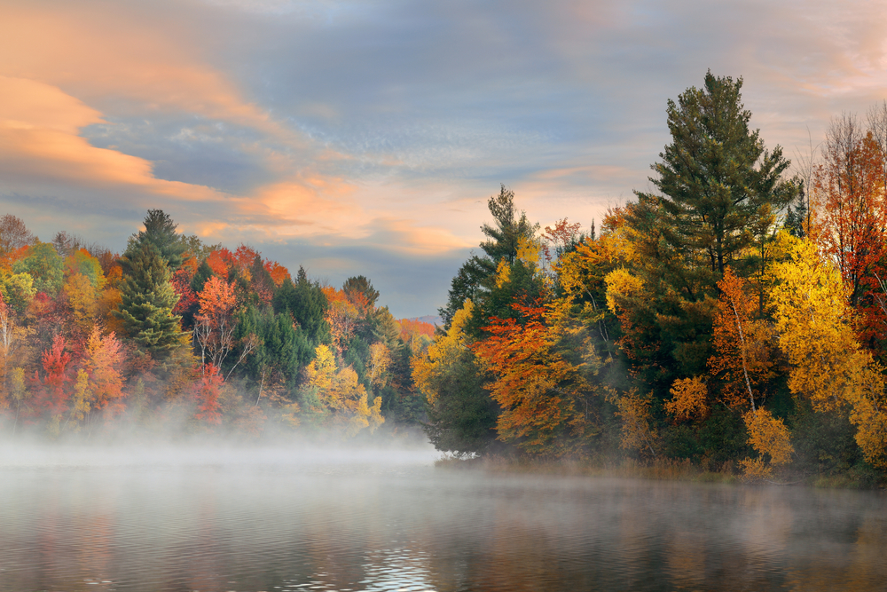 Fog hovers over a lake surrounded by orange, yellow and green trees under a pale orange and blue sky.