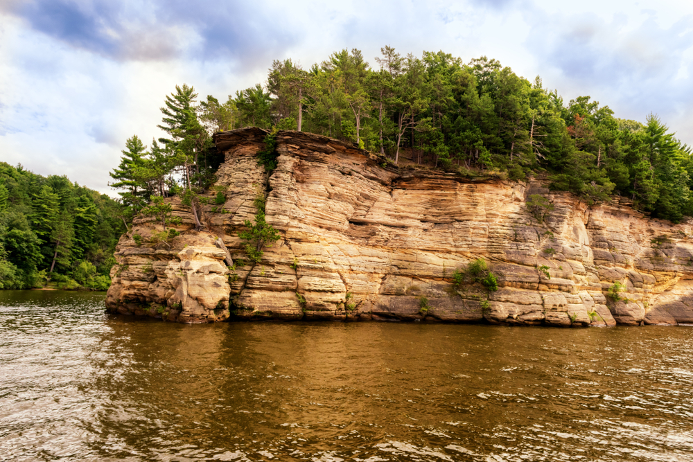 A river flows around a rock formation with trees growing on top of it.
