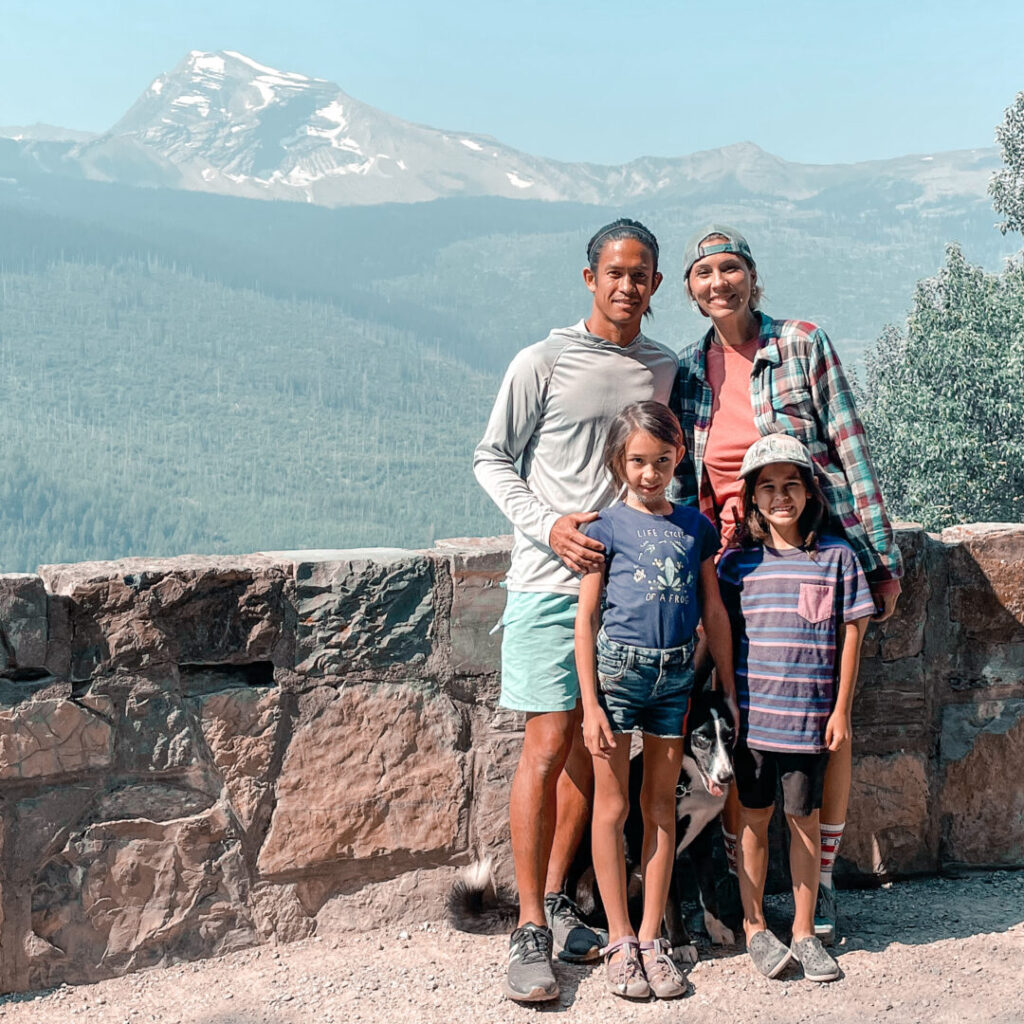 Family of four - mom, dad, son, daughter - poses at Glacier National Park