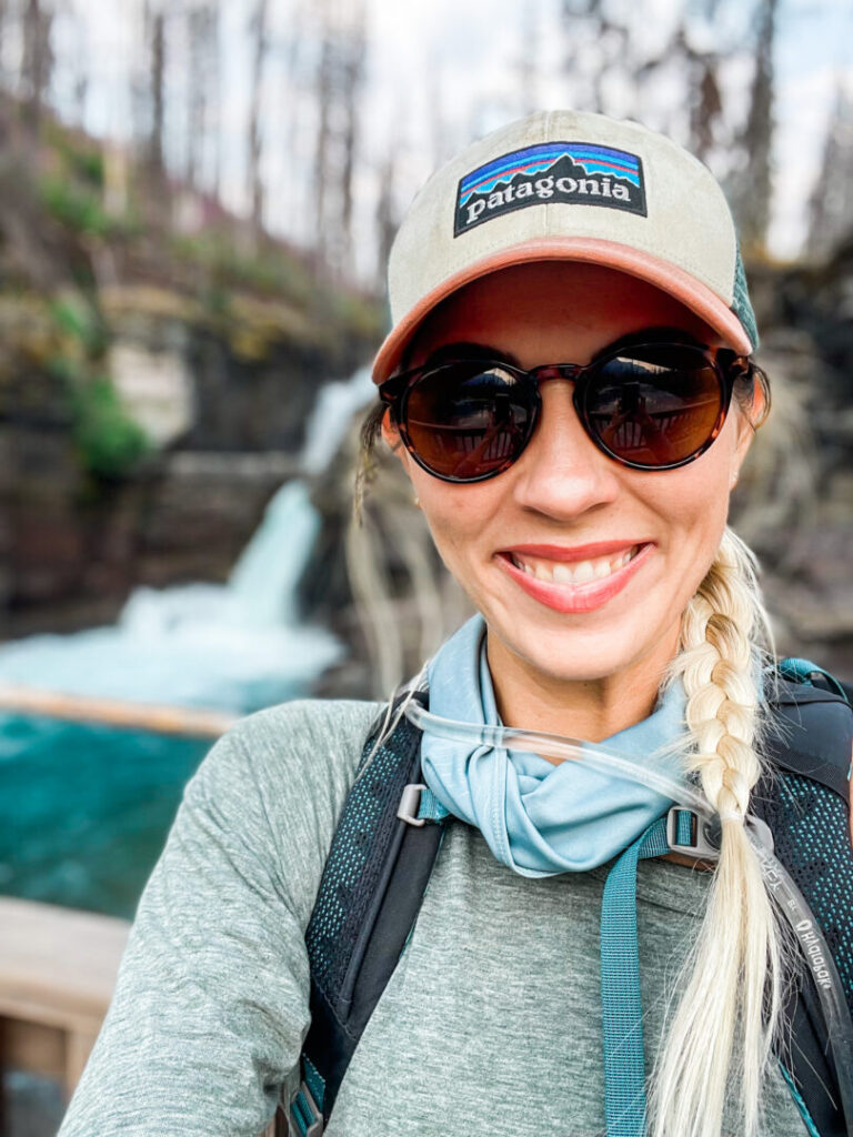 Woman smiles in front of waterfall at Glacier National Park