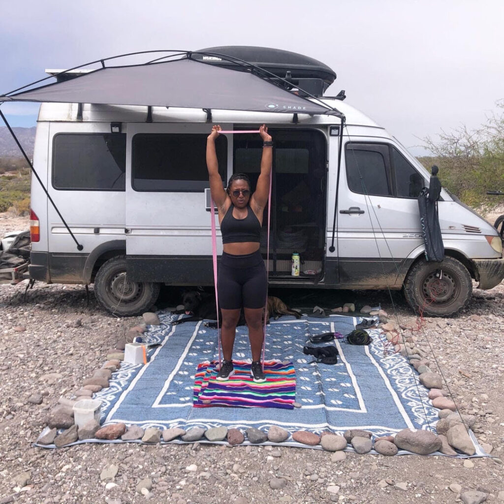 Woman uses exercise band in front of her campervan