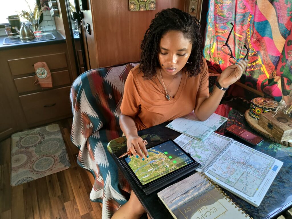 Young woman planning her road trip at the table of her RV