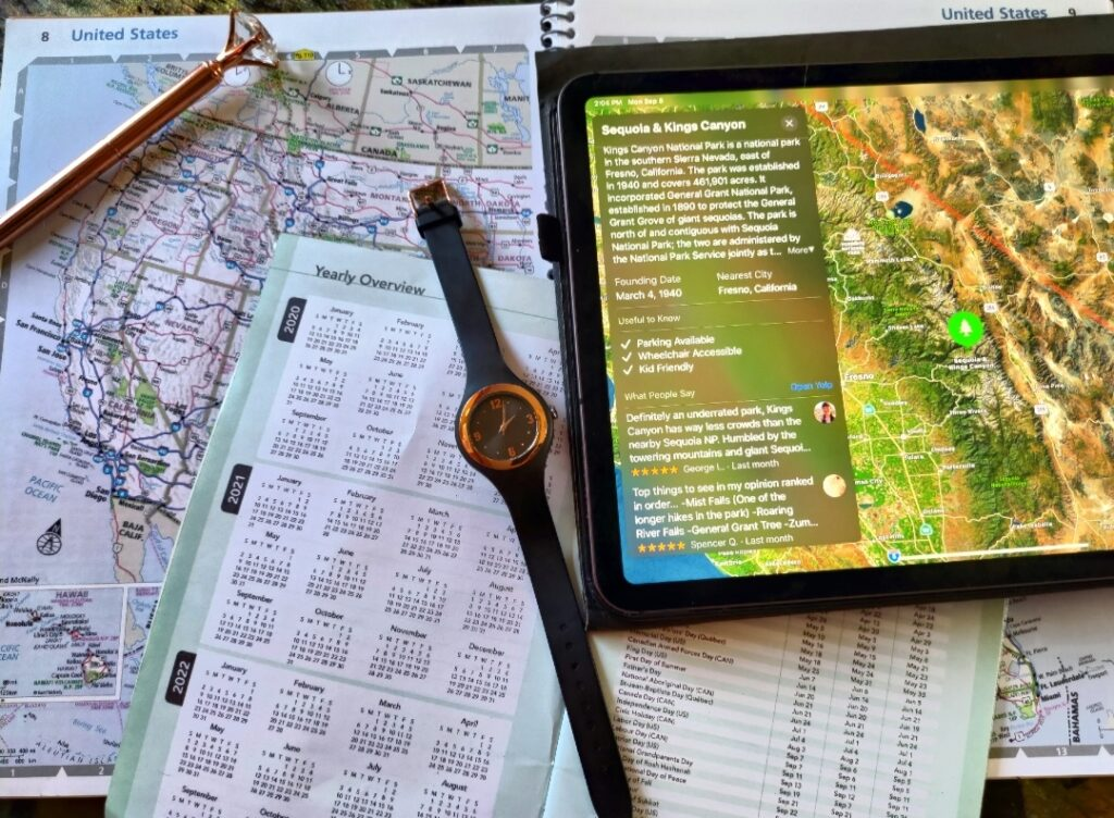 Collection of maps, calendars, and watch on table while trip planning