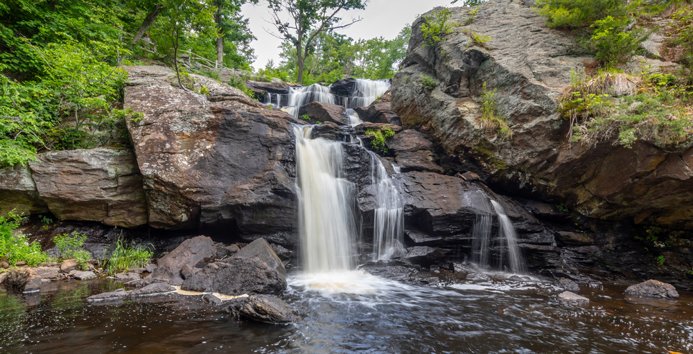 Landscape with waterfall, rocks and leafy green trees at Eightmile River , Chapman Falls, East Haddam, Connecticut Devil's Hopyard State Park