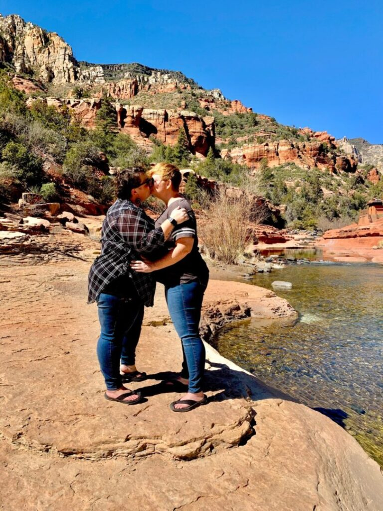 Couple kisses along a river on hike in Arizona