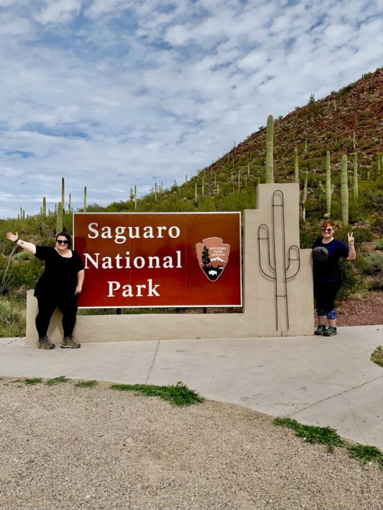 Couple poses in front of Saguaro National Park sign
