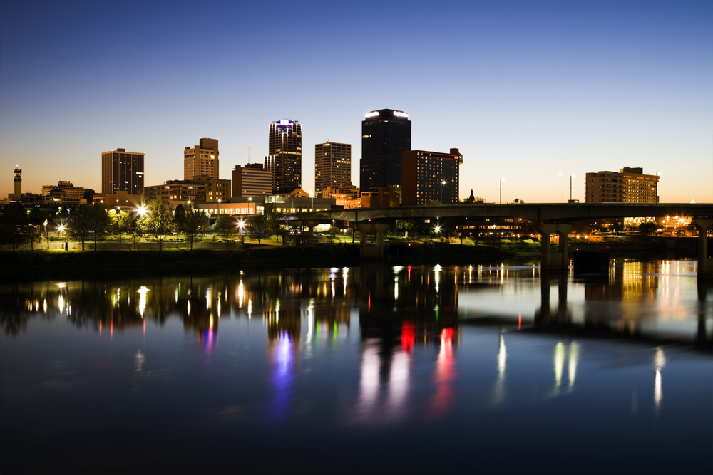The lights and towers of a city skyline during false dawn that are reflected in calm dark waters