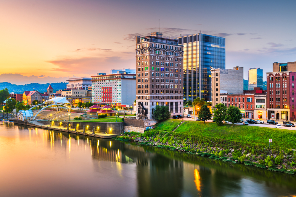 A glowing river at dusk flows along a bank of tall, colorful office buildings with a line of greenery in the foreground
