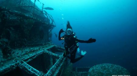Scuba diver poses with sunken ship