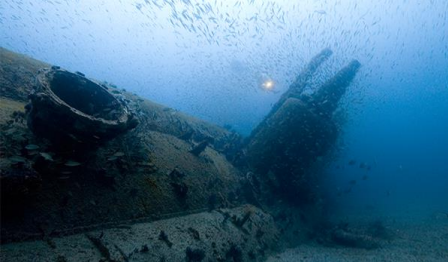 Sunken ship at the bottom of a lake with fish swimming around