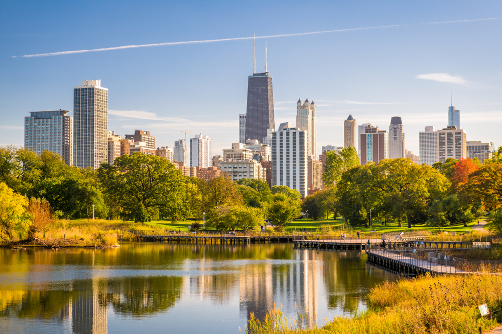 A pond surrounded by grass and autumn colored trees in front of a cityscape under a blue sky with wispy white clouds