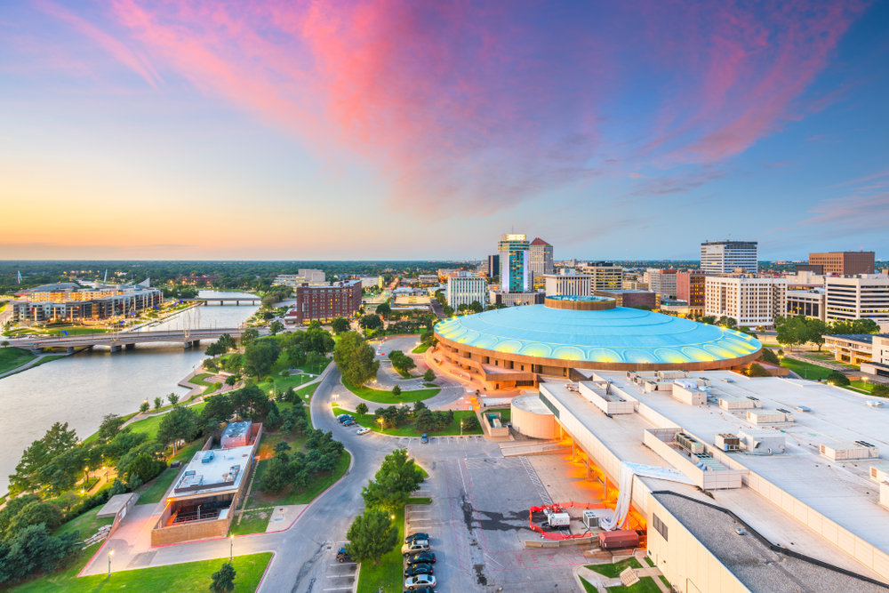 A circular building with a teal roof stands in a city beside a river under a purple and blue sky with pink clouds.